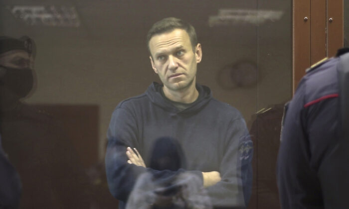 Russian opposition leader Alexei Navalny stands in a cage during a hearing on his charges for defamation, in the Babuskinsky District Court in Moscow, Russia, on Feb. 5, 2021. (Babuskinsky District Court via AP)