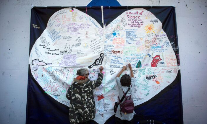 Women write messages on a banner during a memorial service to remember those who have died from drug overdoses in B.C., on International Overdose Awareness Day in Vancouver's Downtown Eastside on Aug. 31, 2017. (The Canadian Press/Darryl Dyck)