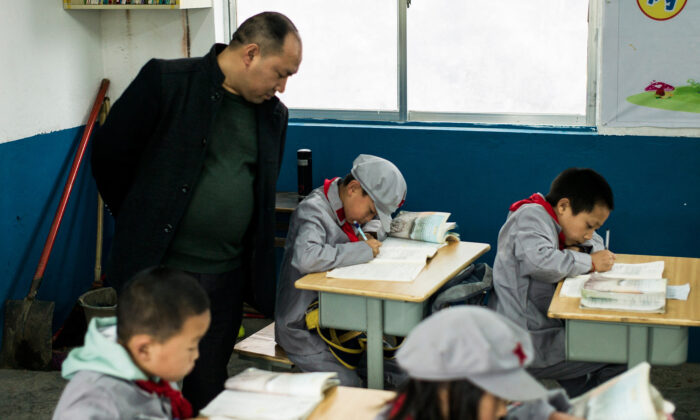 """A teacher supervising students in the Yang Dezhi """"Red Army"""" elementary school in Wenshui, Xishui County, in Guizhou Province, China, on Nov. 7, 2016. (FRED DUFOUR/AFP via Getty Images)"""