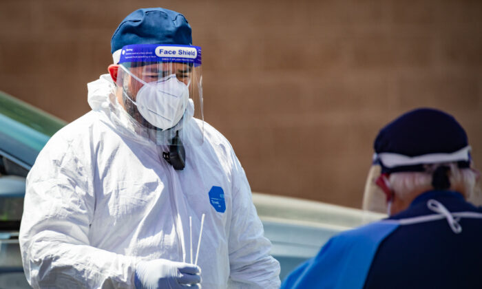 Teledentist Parsia Jahanbani hands an adiministered coronavirus testing kit to medical personal in Anaheim, Calif. on 08.25.2020. (John Fredricks/The Epoch Times)