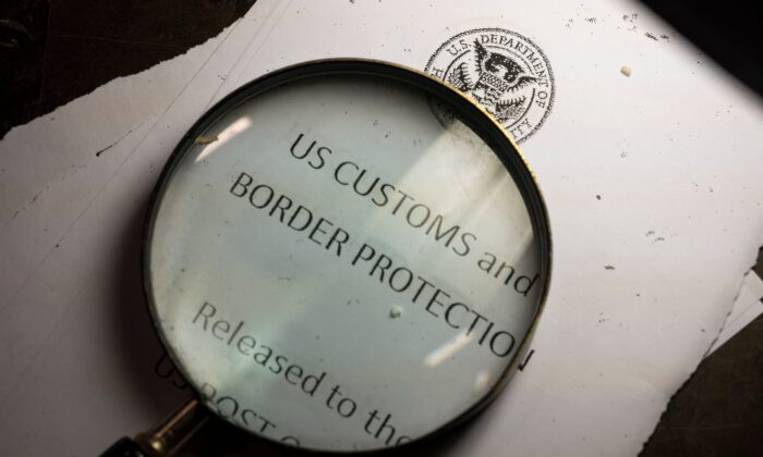 A magnifying glass is seen next to a logo of the Customs and Border Protection, Trade and Cargo Division at John F. Kennedy International Airport's U.S. Postal Service facility in New York on June 24, 2019. (Johannes Eisele/AFP via Getty Images)
