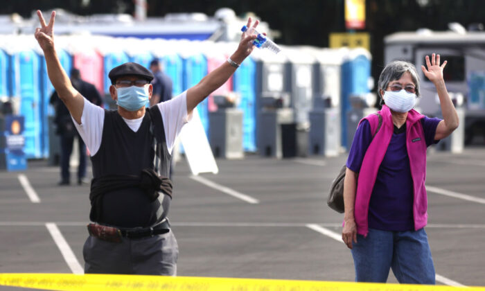 People react after receiving the COVID-19 vaccine at a mass vaccination site in a parking lot for Disneyland Resort on January 13, 2021 in Anaheim, California. (Mario Tama/Getty Images)