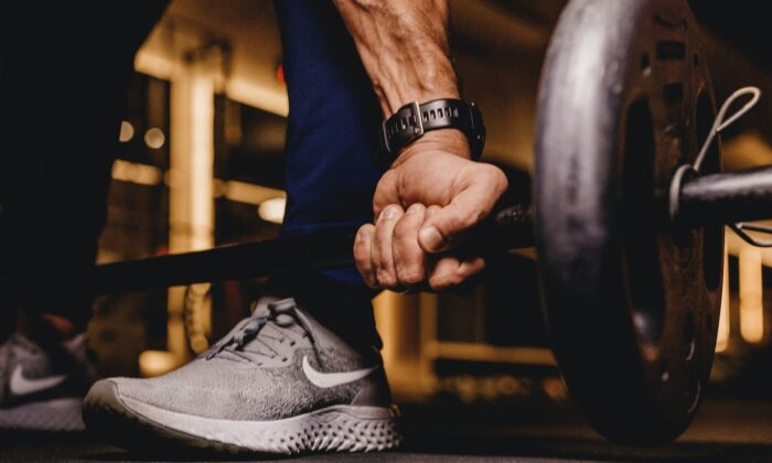 Stock image of a person lifting weights. (Jonathan Borba/Unsplash)