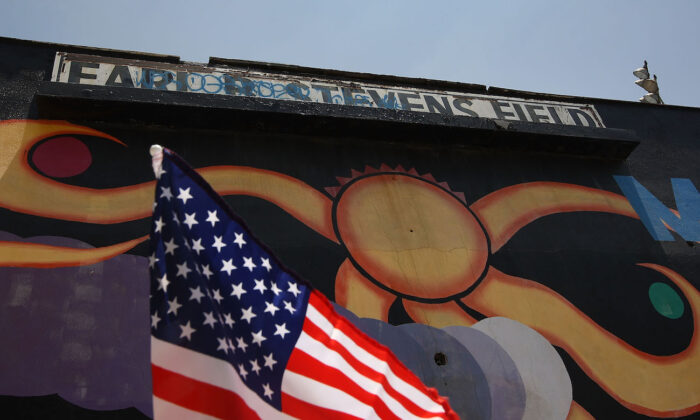 An American flag flies on a car next to a mural at Maywood Park in Maywood, Calif., on June 23, 2010. (David McNew/Getty Images)