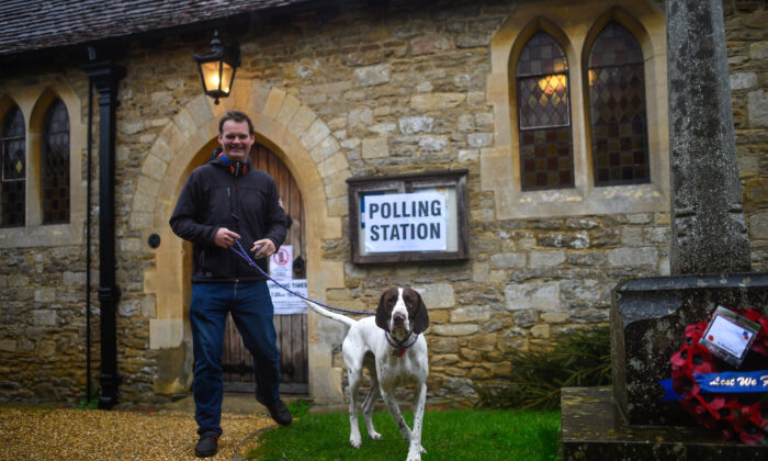 A voter with a dog leaves after casting his ballot paper at a polling station inside a church near Oxford, United Kingdom, on Dec. 12, 2019. (Peter Summers/Getty Images)