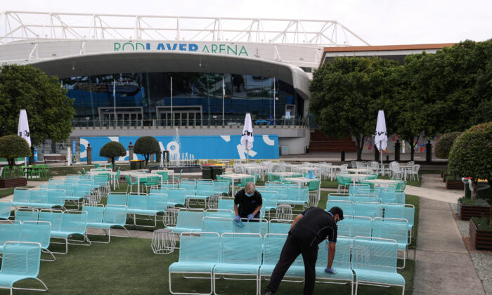 Workers clean a seating area at Melbourne Park in the wake of the day's tennis matches leading up to the Australian Open being cancelled after a hotel quarantine worker at a player hotel tested positive for the coronavirus disease (COVID-19) in Melbourne, Australia, Feb. 4, 2021. (Loren Elliott/Reuters)