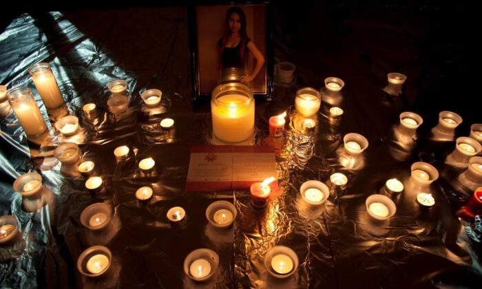 Candles are seen in front of a picture of Amanda Todd during a memorial for her in Surrey, B.C., on Oct. 19, 2012. (The Canadian Press/Jonathan Hayward)