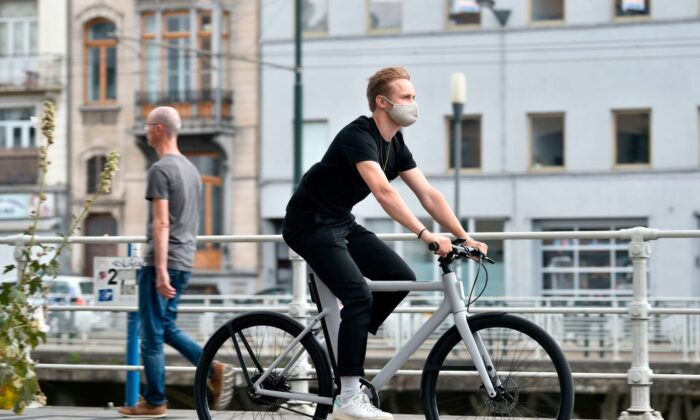 A Cowboy's employee, wearing a protective face mask, rides a Cowboy electric bike in the streets of Brussels, on July 28, 2020. (JOHN THYS/AFP via Getty Images)
