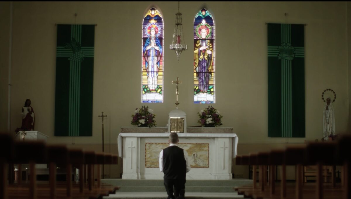 """young man at altar and stained-glass windows in """"Pray"""""""