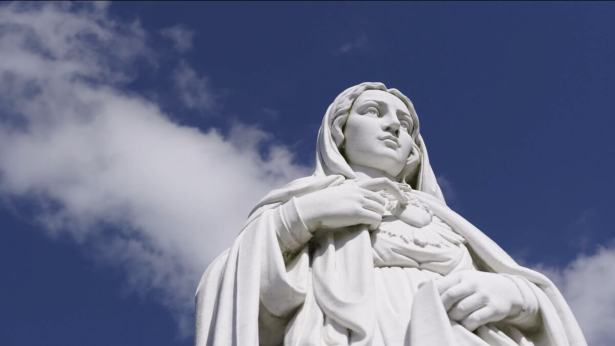 """statue of Mary with clouds and sky background in """"Pray"""""""