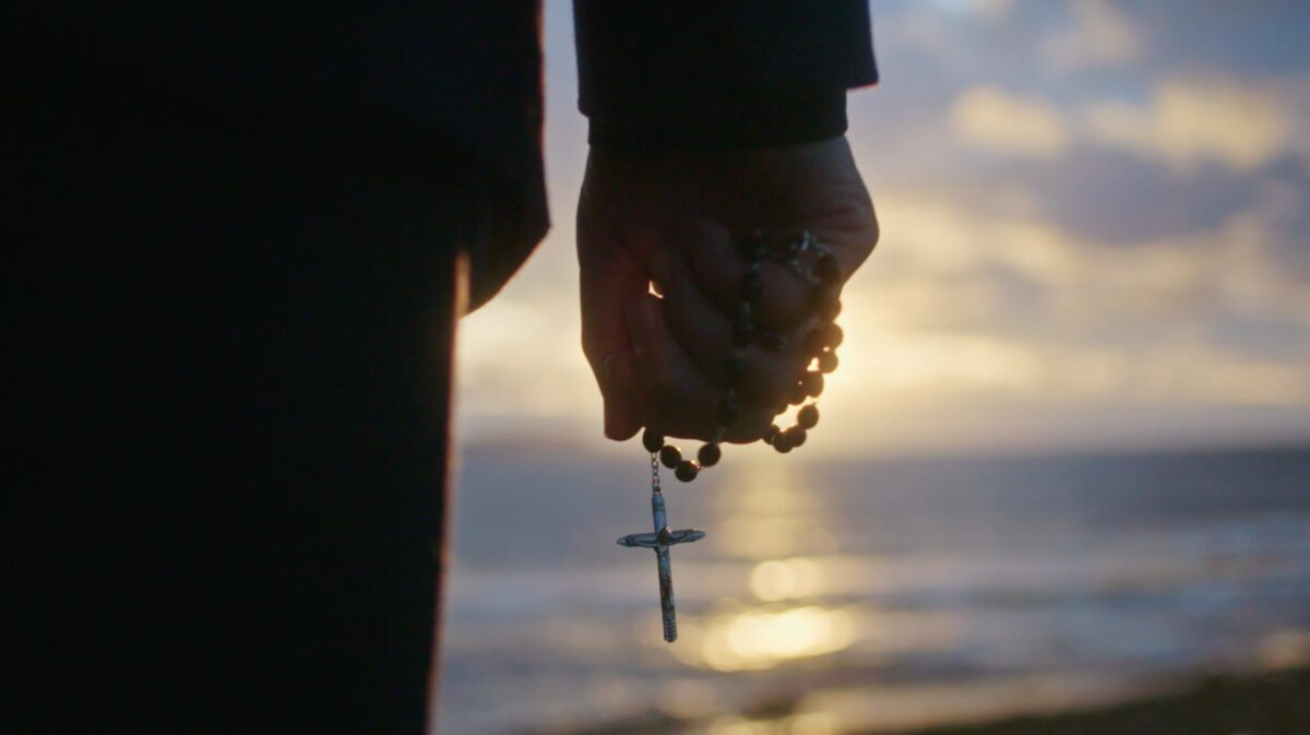 """hand with rosary beads in """"Pray"""""""
