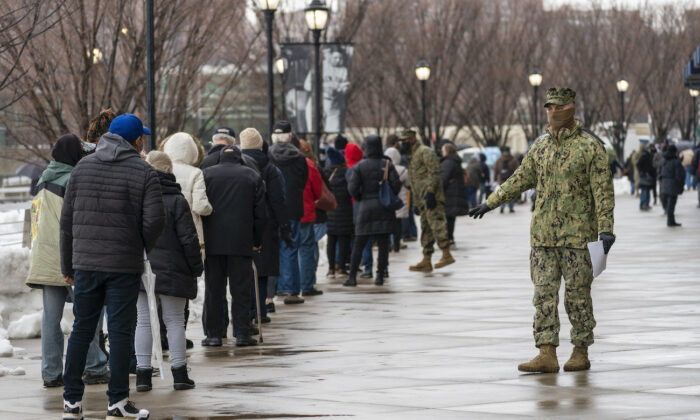 A member of the National Guard gives people direction standing in line at a COVID-19 vaccination site at Yankee Stadium, in the Bronx borough, New York, on Feb. 5, 2021. (AP Photo/Mary Altaffer)