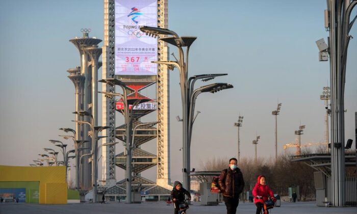 People walk on the Olympic Green near a countdown clock showing the time remaining before the 2022 Beijing Olympics in Beijing on Feb. 2, 2021. (AP Photo/Mark Schiefelbein)
