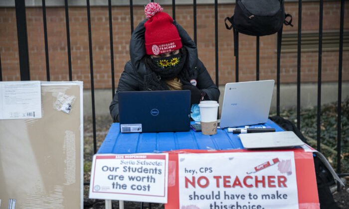 Elementary 1 teacher Melissa Vozar sits outside of Suder Elementary in Chicago to teach a virtual class on Jan. 11, 2021. (Anthony Vazquez/Chicago Sun-Times via AP)