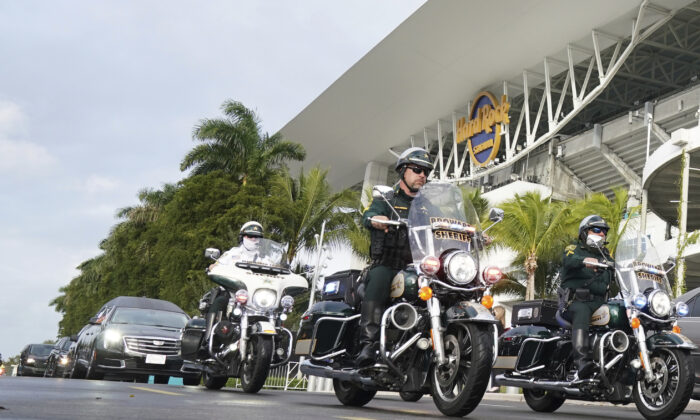 The hearse carrying the casket of FBI Special Agent Laura Schwartzenberger leaves with a police escort after a memorial service at Hard Rock Stadium in Miami Gardens, Fla.,  on Feb. 6, 2021. (Hans Deryk/AP Photo)