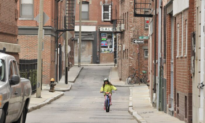 A young girl rides her bike on empty city streets with no school and a lack of tourist due to the coronavirus disease (COVID-19) in Boston, Mass., on March 12, 2020. (Joseph Prezioso/AFP via Getty Images)