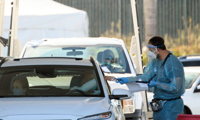 A COVID-19 testing site staff member uses a pulse oximeter to screen a driver at a drive-up testing site at the Orange County Fairgrounds in Costa Mesa, Calif., Nov. 17, 2020. (Patrick T. Fallon/AFP via Getty Images)
