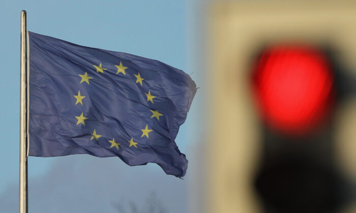 A flag of the European Union waves in the wind near a traffic light showing red in Berlin on Nov. 30, 2011. (Sean Gallup/Getty Images)