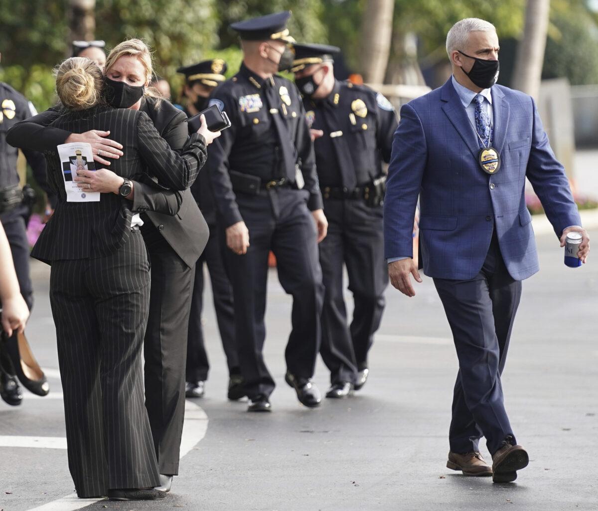 Law enforcement representatives embrace
