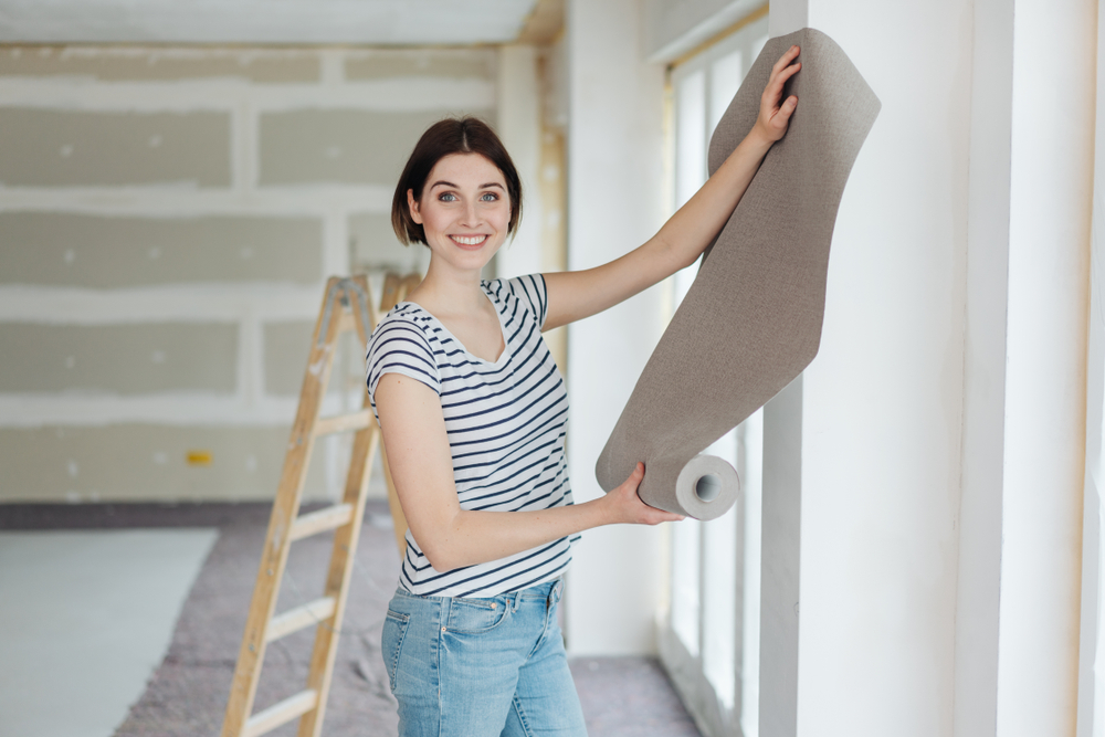 Happy,Young,Woman,Hanging,Wall,Paper,While,Doing,Diy,Home