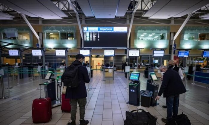 A WestJet employee assists a person checking in for a domestic flight at Vancouver International Airport on Jan. 21, 2021. (Darryl Dyck/The Canadian Press)