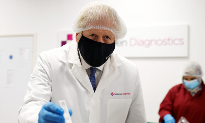 Prime Minister Boris Johnson during a visit to SureScreen Diagnostics in Derby, England, on Feb. 7, 2021. SureScreen Diagnostics supplies a COVID-19 antibody rapid test that is used in combating the pandemic. (Phil Noble - WPA Pool/Getty Images)