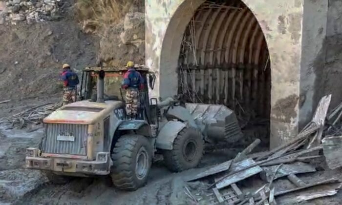 Indo Tibetan Border Police personnel are using machinery to clear mud as they try to rescue more than three dozen power plant workers trapped in a tunnel in the Tapovan area of the northern state of Uttarakhand, India, on Feb. 8, 2021. (Indo Tibetan Border Police via AP)