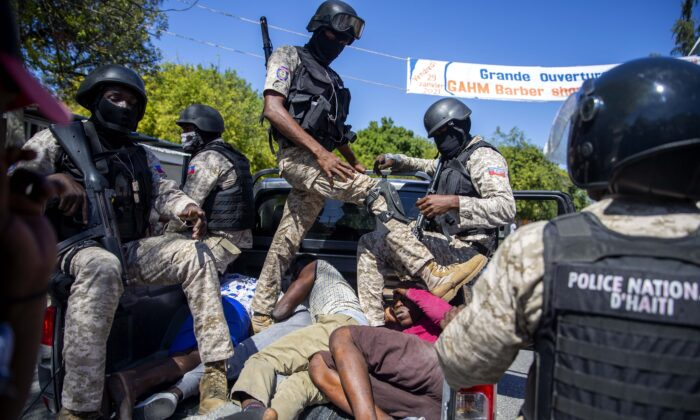 Police move detained demonstrators in the bed of a pick-up truck to a police station during a protest to demand the resignation of Haitian President Jovenel Moise in Port-au-Prince, Haiti, on Feb. 7, 2021. (Dieu Nalio Chery/AP Photo)