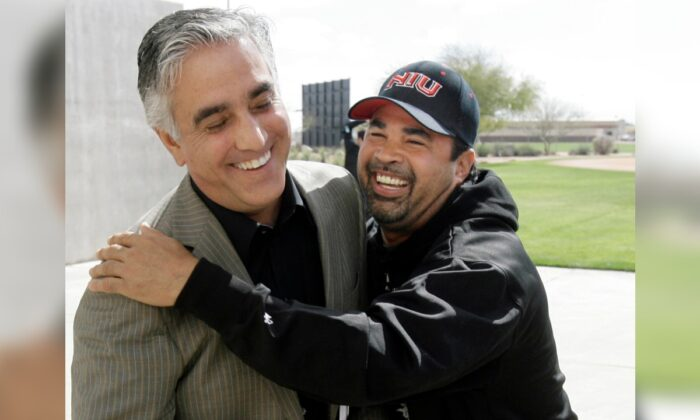 Chicago White Sox manager Ozzie Guillen (R) jokes with ESPN's Pedro Gomez after a news conference during the first day of baseball spring training for pitchers and catchers, in Tucson, Ariz., on Feb. 16, 2008. (M. Spencer Green/File/AP Photo)