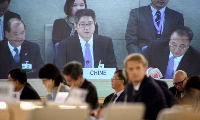 Chinese Vice Minister of Foreign Affairs Le Yucheng (C) is seen on a giant TV screen delivering a speech before the United Nations (UN) Human Rights Council in Geneva, on Nov. 6, 2018. (Fabrice Coffrini/AFP via Getty Images)