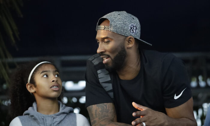 Former Los Angeles Laker Kobe Bryant and his daughter Gianna watch the U.S. national championships swimming meet in Irvine, Calif., on July 26, 2018. (Chris Carlson/AP Photo)