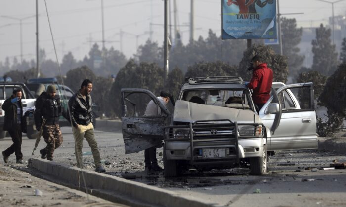 Security personnel inspect the site of a bomb attack in Kabul, Afghanistan, on Feb. 2, 2021. (Rahmat Gul/AP Photo)