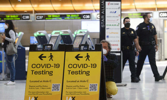 A traveler takes a photo of a COVID-19 testing sign at the Tom Bradley International Terminal, in Los Angeles, Calif., on Feb. 4, 2021. (Patrick T. Fallon/AFP via Getty Images)