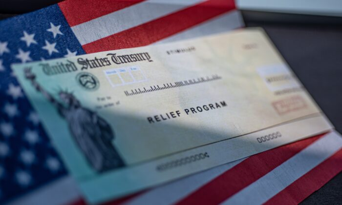 COVID-19 economic Stimulus check on blurred USA flag and sun light background. Relief program concept. (Shutterstock)