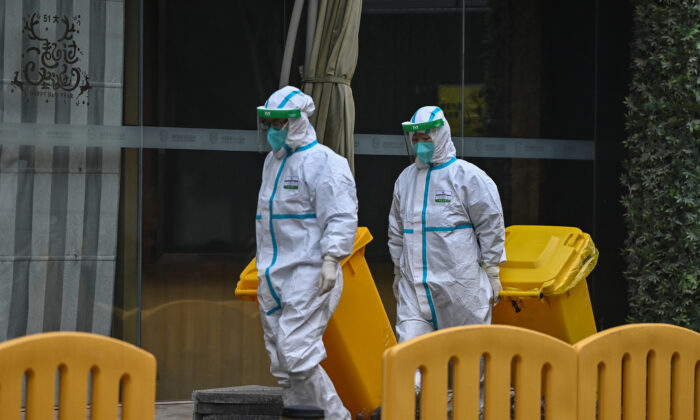 Workers wearing protective gear are seen in the compounds of The Jade Boutique Hotel, where members of the World Health Organization (WHO) team investigating the origins of the COVID-19 pandemic are due to complete their quarantine, in Wuhan, China, on Jan. 28, 2021. (Hector Retamal/AFP via Getty Images)