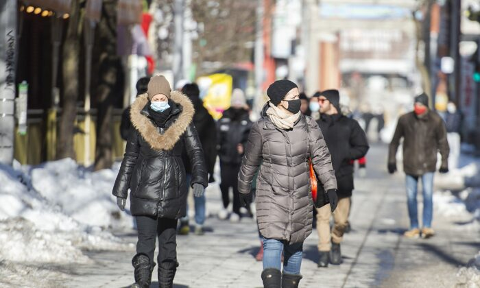 People walk along a street in Montreal on Jan. 31, 2021. Post-COVID, the federal and provincial governments must develop long-term plans to meaningfully address the growing debt problem in Canada, a new report suggests.  (The Canadian Press/Graham Hughes)