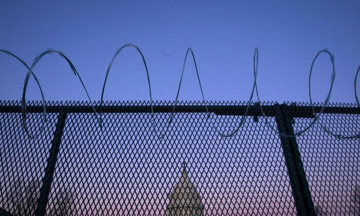 The U.S. Capitol building is seen through barbed wire fencing at sunrise in Washington on Feb. 8, 2021. (Sarah Silbiger/Getty Images)