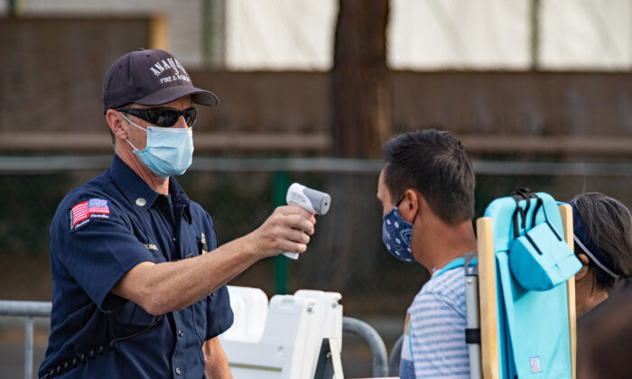 An Anaheim firefighter checks temperatures at a COVID-19 vaccination center set up in a parking area of Disneyland themepark in Anaheim, Calif., on Jan, 13, 2021. (John Fredricks/The Epoch Times)