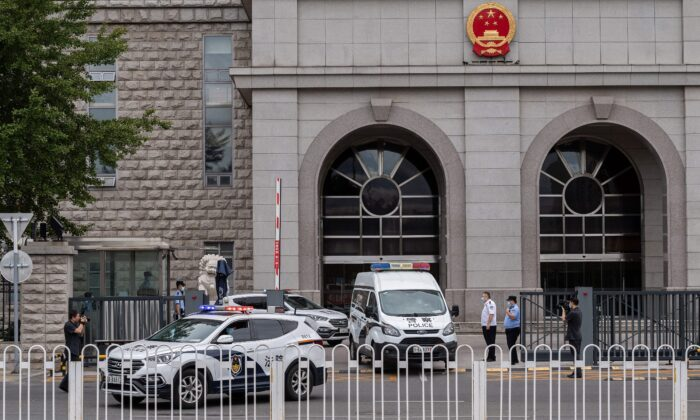 Police vans parked outside a court in Beijing on Sept. 11, 2020. (NICOLAS ASFOURI/AFP via Getty Images)