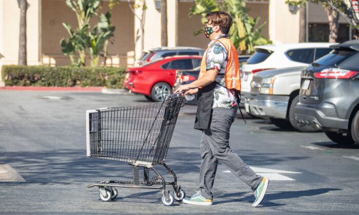 A worker at Ralphs returns a shopping cart to the store in Irvine, Calif., on Feb. 5, 2021. (John Fredricks/The Epoch Times)