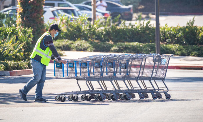A worker pushes shopping carts in a Walmart parking lot in Irvine, Calif., on Feb. 5, 2021. (John Fredricks/The Epoch Times)