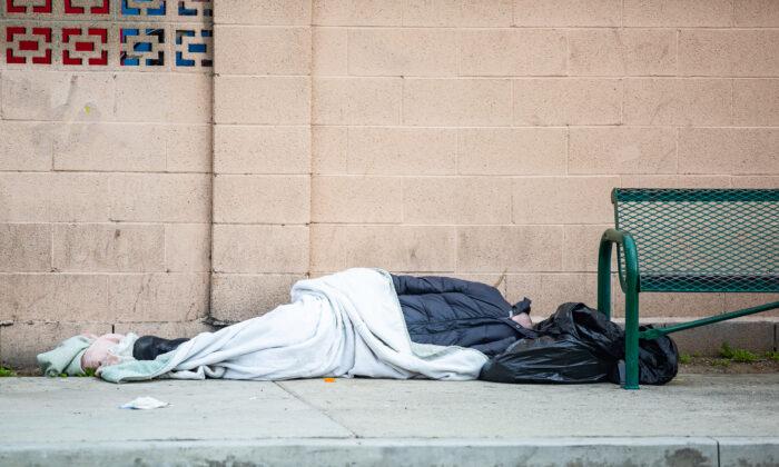A homeless person sleeps near West First Street and Fairview, in Santa Ana, Calif.,  on Feb. 9, 2021. (John Fredricks/The Epoch Times)