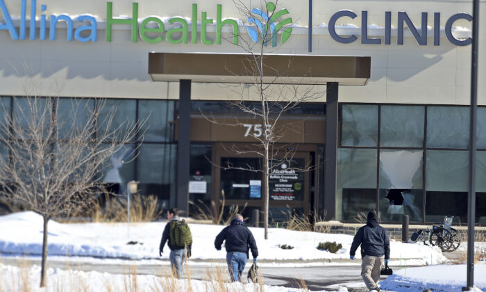 Law enforcement personnel walk toward the Allina Health clinic in Buffalo, Minn., on Feb. 9, 2021. (David Joles/Star Tribune via AP)