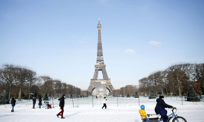People walk and ride a bicycle on a snow covered alley near the Eiffel Tower, in Paris, France, on Feb. 10, 2021. (Thibault Camus/AP Photo)