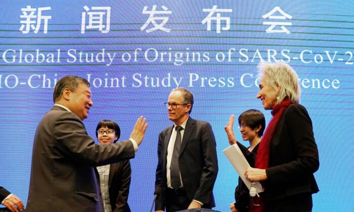 Marion Koopmans, right, and Peter Ben Embarek, center, of the World Health Organization team say farewell to their Chinese counterpart Liang Wannian, left, after a WHO-China Joint Study Press Conference held at the end of the WHO mission in Wuhan, China, on Feb. 9, 2021. (AP Photo/Ng Han Guan)