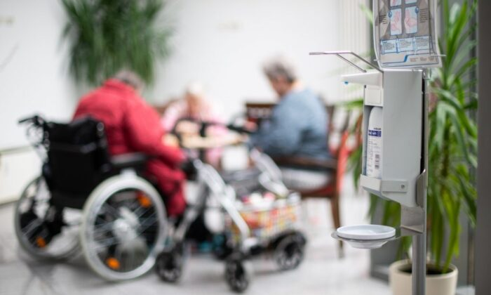 Residents sit near a hand sanitizer dispenser at a long-term care home. (Photo by Jonas Güttler/Picture Alliance via Getty Images)