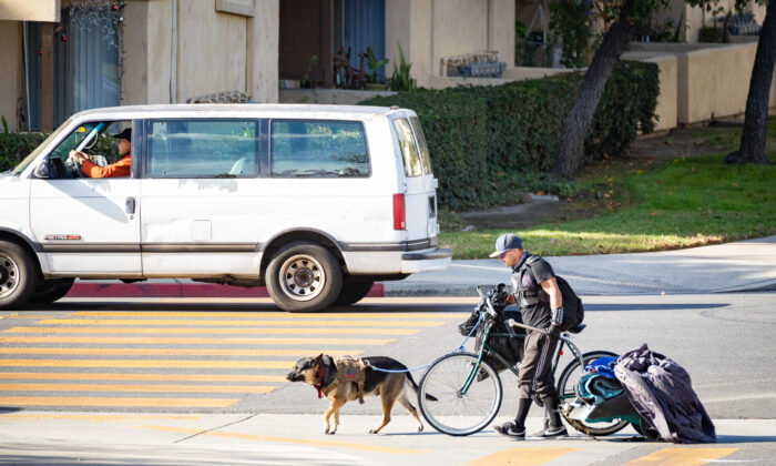 A homeless man walks with his bike, dog, and possessions in Santa Ana, Calif., on Dec. 17, 2020. (John Fredricks/The Epoch Times)