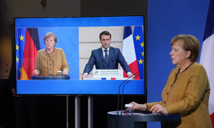 German Chancellor Angela Merkel and French President Emmanuel Macron, who is tuning in from Paris via video link, speak to the media following talks in Berlin on Feb. 5, 2021. (Sean Gallup/Getty Images)