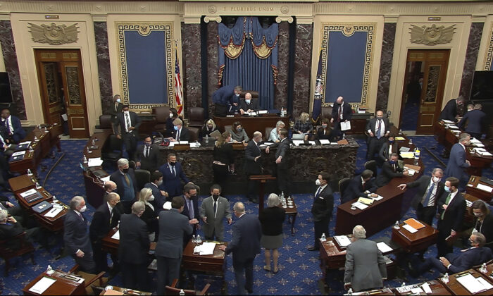 In this image from video, senators gather around Senate Majority Leader Chuck Schumer (D-N.Y.) amid confusion about a request to strike comments from the record, in Washington on Feb. 10, 2021. (Senate Television via AP)