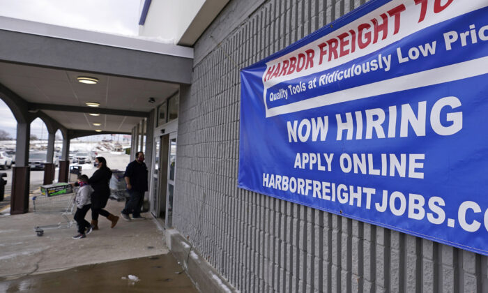 """A """"Now Hiring"""" sign hangs on the front wall of a Harbor Freight Tools store in Manchester, N.H., on Dec. 10, 2020. (Charles Krupa/File/AP Photo)"""
